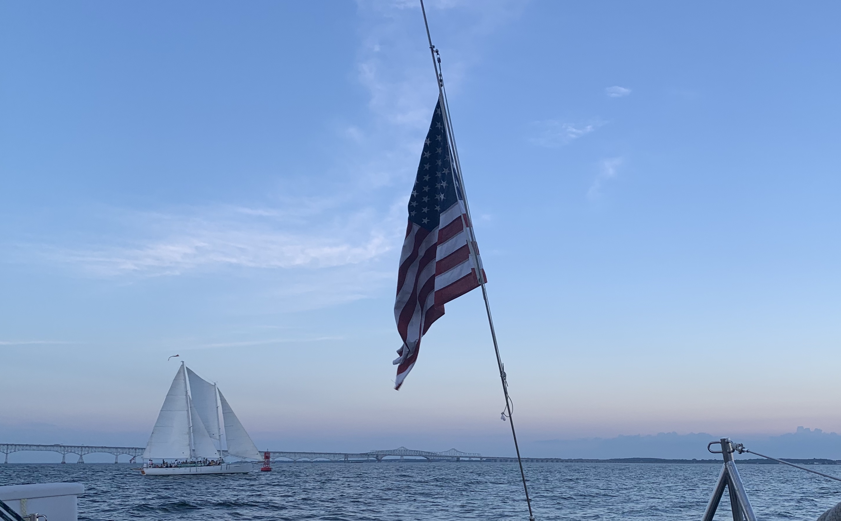 Bay Bridge with Woodwind sailing by it and American Flag