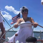 Women in captain's hat steering boat
