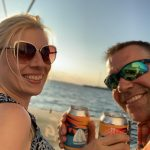 Two Guests holding up Seas the Bay IPA cans and smiling