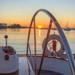 Schooners large silver steering wheel reflecting bright orange sunset