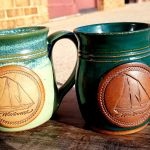 Two Pottery Mugs with the Schooner Woodwind embossed in a circle on the front. One mug is light green the other is dark green