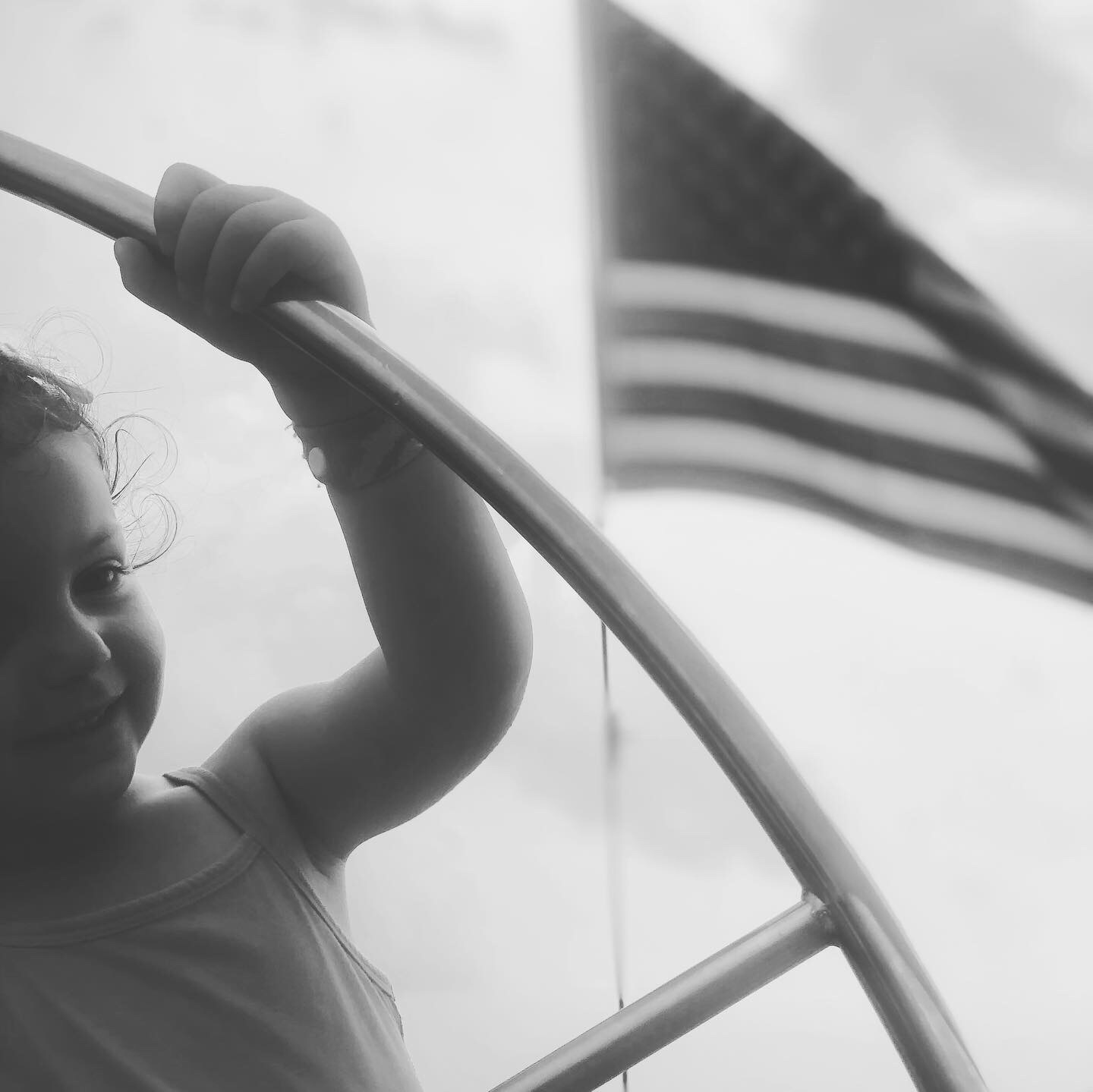 Black and white photograph of little one steering the helm of the schooner