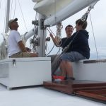 Two young guests getting lesson on raising the sails