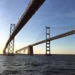 Both spans of the Bay Bridge with blue skies and water
