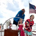 Man and two little girls steering the helm and looking out for pirates