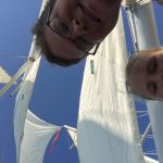 Two guests taking selfie with white sails and blue skies above