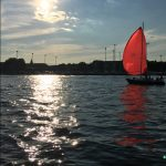 Red sail on a sailboat at sunset