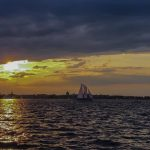 Dark clouds with a bright yellow sunset showing and dark waters with schooner sailing on them