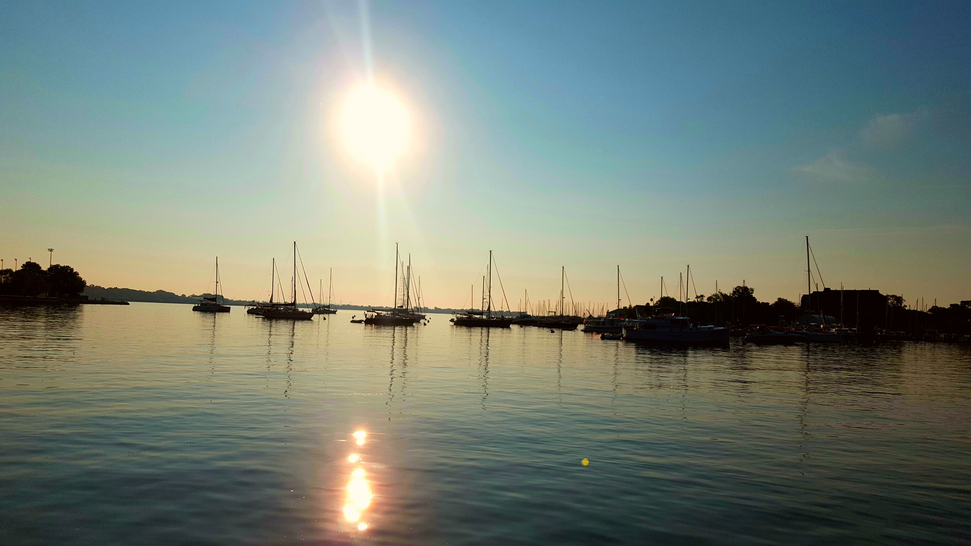 Sun coming up over the calm waters and moored boats in the harbor