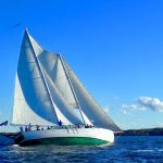 Blue water and blue sky with schooner flying on the water
