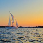 Schooner framed by mellow yellow sunset and blue waters